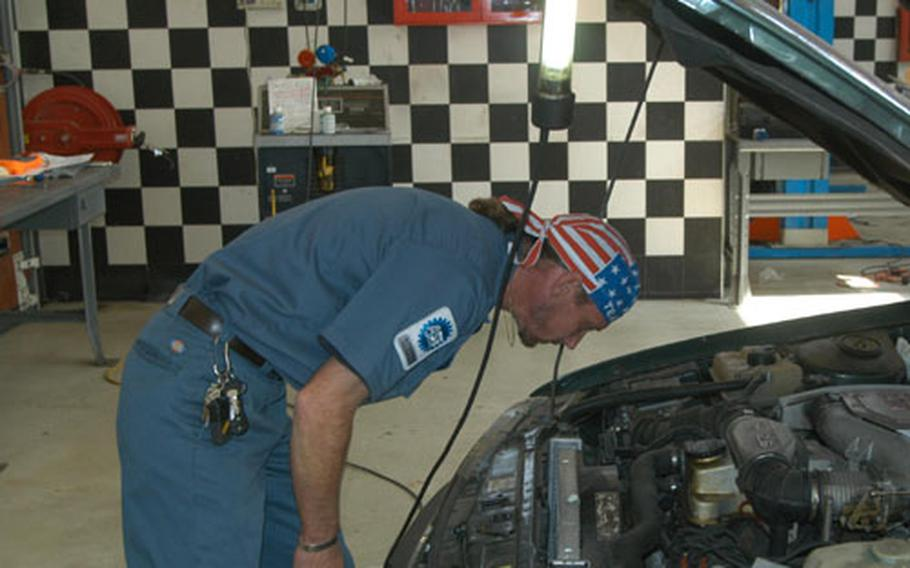 Howie Overacker, one of three employees at Vicenza's auto skills center, looks at a car brought into the shop Wednesday. The center has been selected as the Army's best medium-sized facility for 2004.