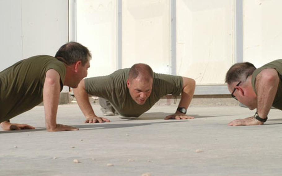 Navy chief petty officer selectees, from left, Jeff Cavallo, Roger Teel and Billy Hammond do push-ups Monday as part of their initiation process. The three sailors are assigned to the 11th Marine Expeditionary Unit at Camp Duke, Iraq.
