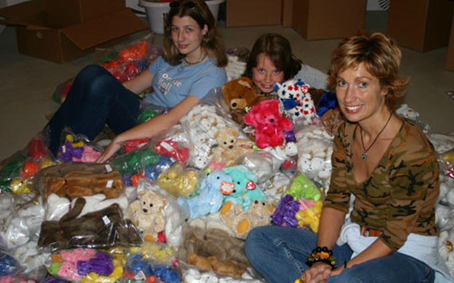 Sandra Hummel, far right, sits among some of the more than 1,600 stuffed bears she has collected for distribution to injured Iraqi children. With her are two daughters, Veneé, 14, left, and Darnelle, 10, who help her with the project. The bears come from donors in the United States and a collection box at the Café Rohr on Ledwards Barracks in Schweinfurt, Germany.