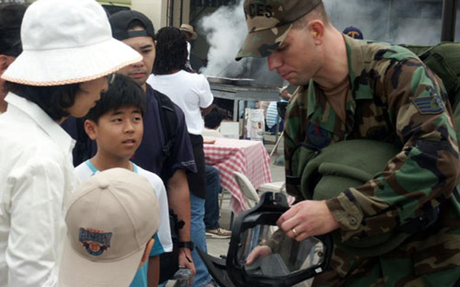 Staff Sgt. Justin Surran, 35th Civil Engineer Squadron, Misawa Air base, Japan, shows a Japanese family a uniform used to detonate explosive ordnance during Airfest 2004.
