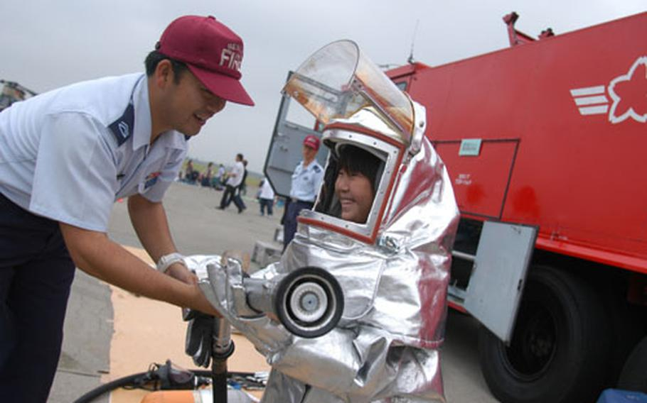 Seizo Takahashi of Miyagi Prefecture tries on Japan Air Self-Defense Force firefighting gear at Sunday's Misawa Air Festival, hosted by the U.S. Air Force and JASDF.