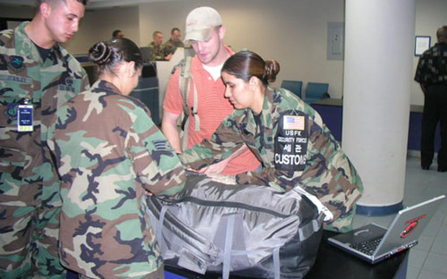 Customs airmen inside passenger terminal at Osan Air Base in South Korea go through baggage of just-arrived servicemember Thursday morning. The airmen, members of Osan's 51st Security Forces Squadron, are part of a team that works to prevent outlawed items from getting into South Korea. At right is Staff Sgt. Lisa Rodriguez, the team's noncomissioned officer-in-charge; center is Senior Airman Cristina Chomina, a customs inspector; left is Senior Airman Anthony Stanley, customs inspector in training.