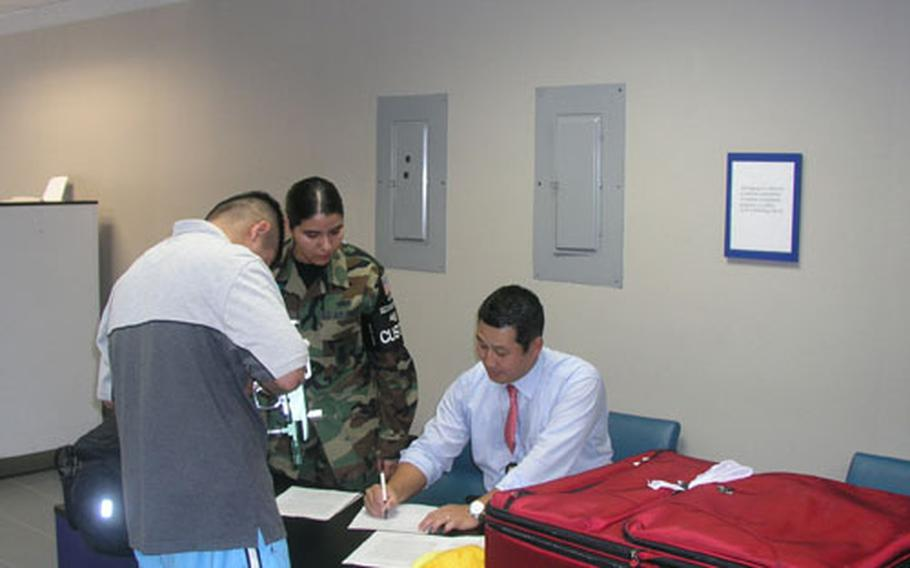 Customs inspectors at Osan Air Base in South Korea fill out paperwork before confiscating a servicemember's paintball gun. The owner has 30 days to file to reclaim the item. Seated is Rayond Park, an Osan-based customs inspector with United States Forces Korea. Standing, in unfiorm, is Air Force Staff Sgt. Lisa Rodriguez of Osan's 51st Security Forces Squadron. She's noncommissioned officer-in-charge of a customs team that works the Osan terminal. (pnw# 61p cs)