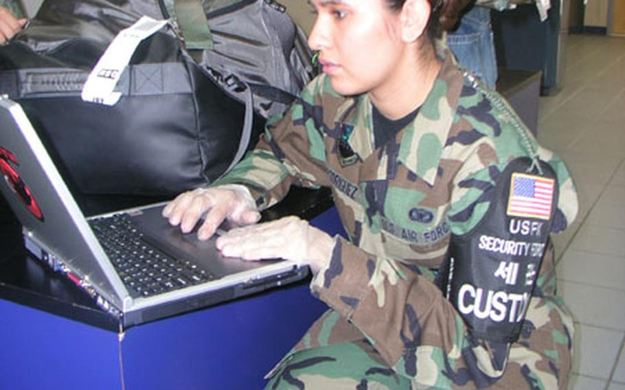 Inside the passenger terminal at Osan Air Base, South Korea Thursday, Air Force Staff Sgt. Lisa Rodriguez checks a passenger's laptop for possible pornographic images. Rodriguez, of Osan's 51st Security Forces Squadron, is noncommissioned officer-in-charge of a customs team that works to prevent outlawed items from getting into South Korea.