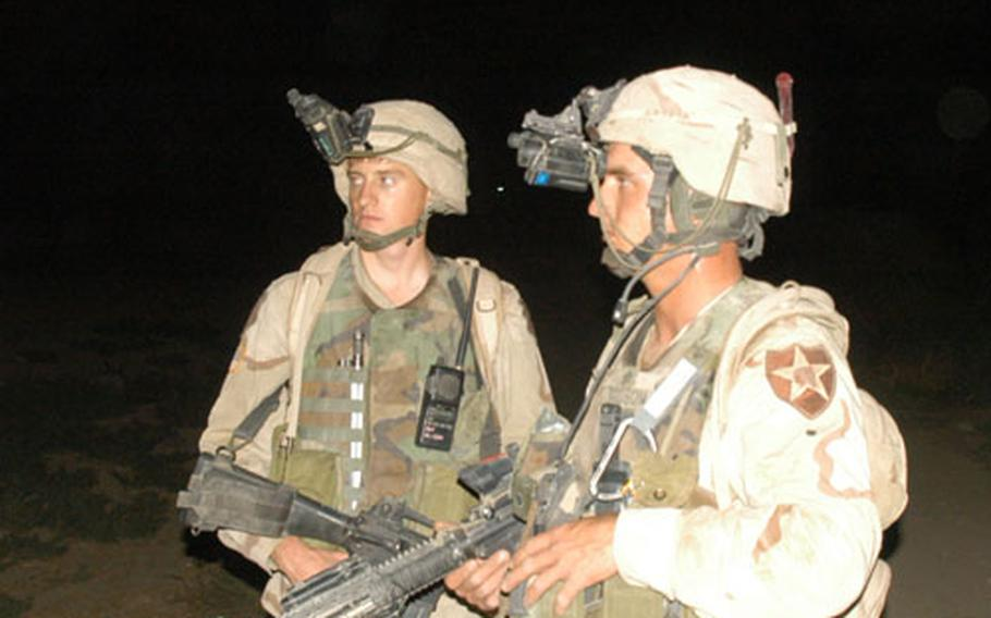 From left: Sgt. George Womack, 27, of Mount Vernon, Wis., (unit information withheld at the request of Strike Force) and Mitch Dodson, 25, of the 2nd Infantry Division's Company C, 1st Battalion, 9th Infantry Regiment, and of Elsmore, Kan., patrol in the dark in the Manchus' new area of operations in Iraq.
