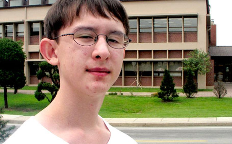 Nathan Carswell, 13, stands across the street from Osan American High School at Osan Air Base in South Korea. Nathan and his parents are anxiously awaiting Sept. 13, when school officials will tell them whether any vacancies have opened up.