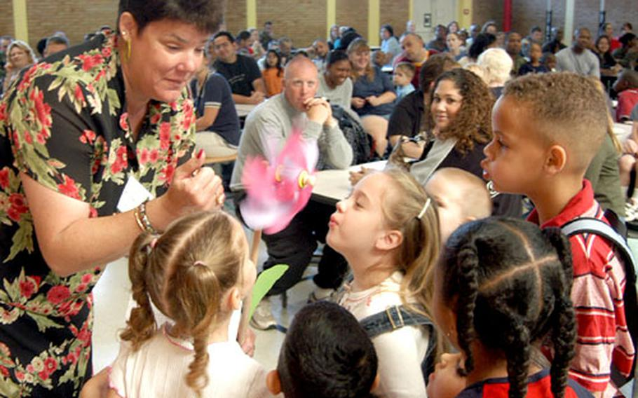 Kindergarten pupils blow on a pinwheel — signifying the winds of change — held by principal Shawne Cryderman at an assembly with parents before the first day of school at Mannheim Elementary.
