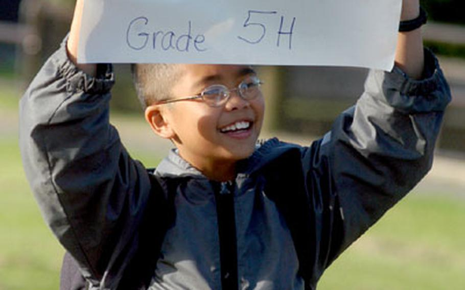 Andrew Luong, a fifth-grader at Alconbury Elementary School, RAF Alconbury, England, holds a sign telling his classmates where to congregate before the school's first day of classes on Tuesday.