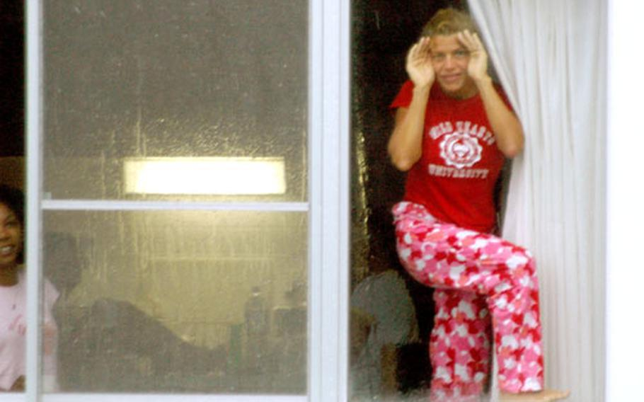 Some Sasebo personnel living off base in older homes were extended an invitation from commander Capt. Michael James to stay on base in bachelor housing. As Typhoon Songda was heavily huffing and puffing Tuesday morning, this young woman stood in a BOH window, trying to get a good look at the wild weather.