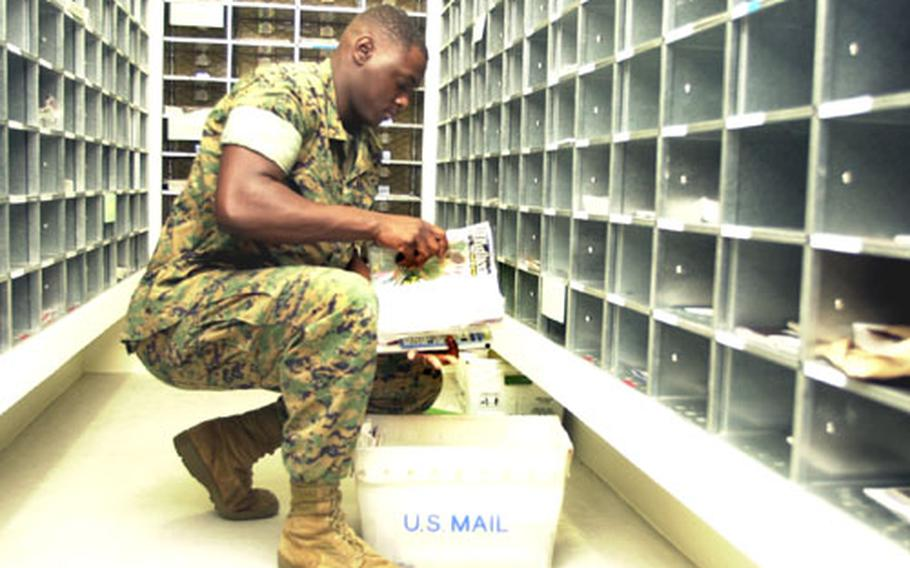 Lance Cpl. Deon Scott, postal clerk, sorts through magazines and catalogs before placing them in mailboxes in the new Camp Foster Post Office.