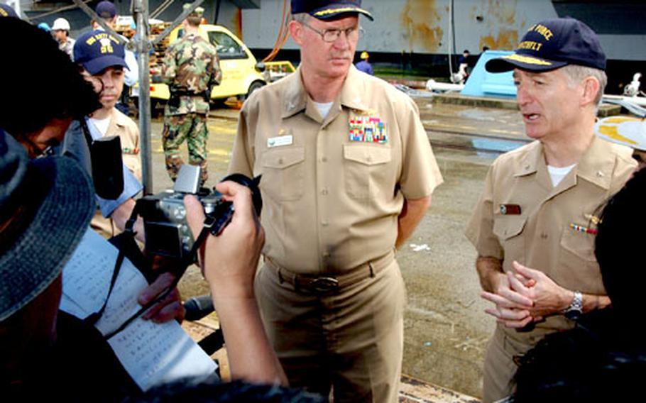 Rear Adm. James D. Kelly, right, commander of the Kitty Hawk Strike Group, stands with Capt. Thomas A. Parker, USS Kitty Hawk commanding officer, as they conduct an interview with local Japanese media.