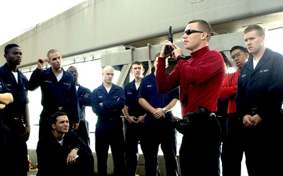 Petty Officer 2nd Class Brenton Davis of Meadville, Pa., a gunner's mate, holds training on the 9mm pistol for a group of sailors preparing to qualify on the weapon. Sailors are required to qualify to shoot a 9mm pistol prior to standing any armed watches in port.