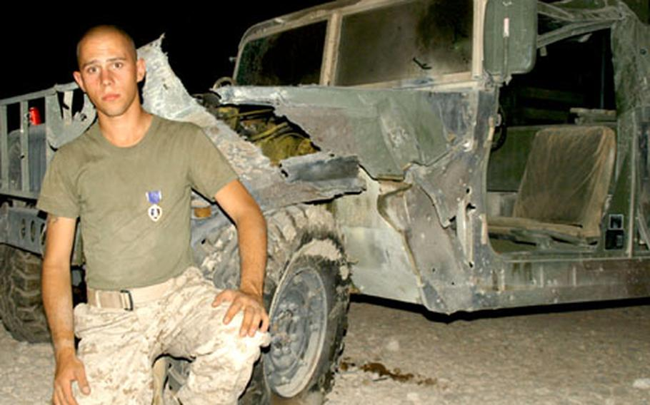 Marine Lance Cpl. Steven Klimtzak of the 4th Civil Affairs Group became the first servicemember of Strike Force — the 2nd Infantry Division's 2nd Brigade Combat Team — to receive a Purple Heart in Iraq. A bomb hit his Humvee, shown in the background.