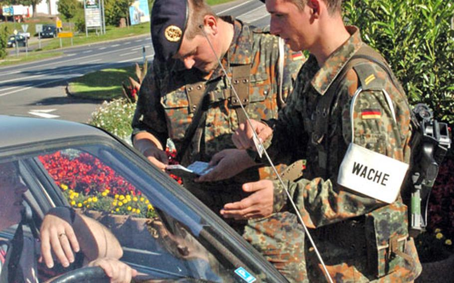 German navy Bundeswehr members check identification before allowing entry at Spangdahlem Air Base's old main gate. The German navy took over gate control duties at the Germany base from the German army Bundeswehr on Thursday.