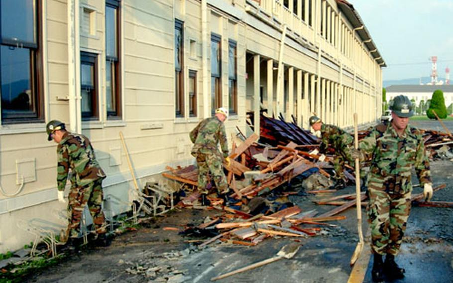 Servicemembers collect debris Wednesday following Typhoon Songda, which blew off about half of the roof at Iwakuni Marine Corps Air Station's Logistics Building the night before.