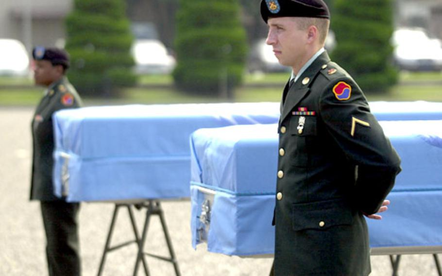 Soldiers stand guard next to the remains of US servicemembers killed in the Korean War.