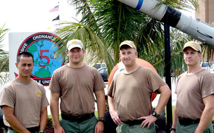 """Four members of EODMU5 stand at the entrance to the unit's compound in Guam following their return from Iraq. They are, left to right, Seaman James """"Kimo"""" Makaneole, Petty Officer 1st Class Tyler Borgwardt, Lt. Will Ranney and Petty Officer First Class Jeffrey Gates."""