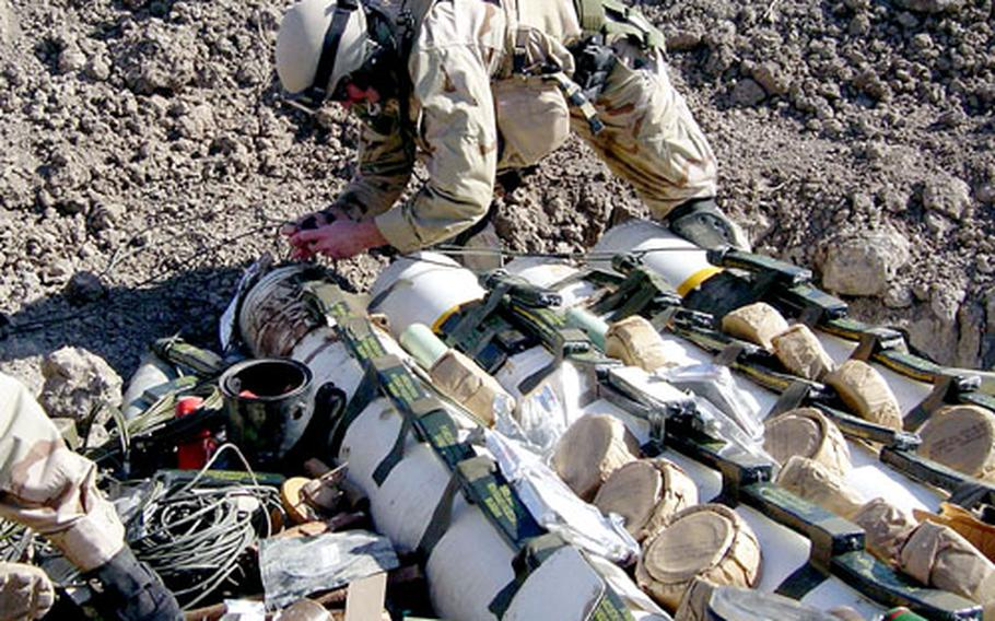 Petty Officer 1st Class Jeffrey Gates disposes of ordnance in Iraq. Gates is now back in Guam with his family.