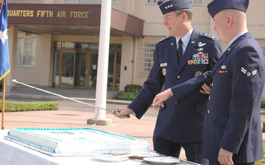 Lt. Gen. Thomas Waskow, left, commander of the 5th Air Force and U.S. Forces Japan, and Airman 1st Class Phillip Haynes of the 20th Operational Weather Squadron take part in the cake-cutting ceremony Friday morning at Yokota Air Base, Japan, which traditionally includes the youngest and most senior airmen present. The event marked the Air Force's 57th birthday and 63rd anniversary of the 5th Air Force as a numbered unit.