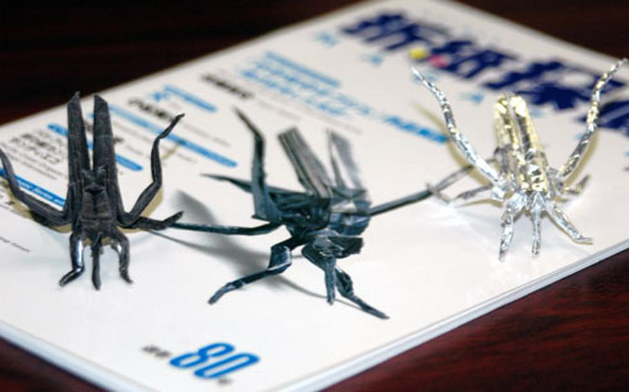 These three mosquitoes are each made from a single piece of paper, 6 inches by 6 inches, and never cut or torn. Origami master Scott Macri, 18, a senior at Ernest J. King High School at Sasebo Naval Base, made the one on the left and the silver one on the far right. The mosquito at center is a cover photograph on a Japanese origami magazine made using the same design pattern. Macri started making various folded paper figures since age seven, when his father, Cmdr. Paul Macri, gave him his first basic origami instructional book.