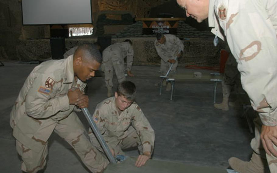 Soldiers work to set up Army cots in the warehouse being used as the ESPN SportsCenter studio. The cots are being used as benches. Dozens of soldiers took part in the construction and decoration of the studio and EPSN offices.