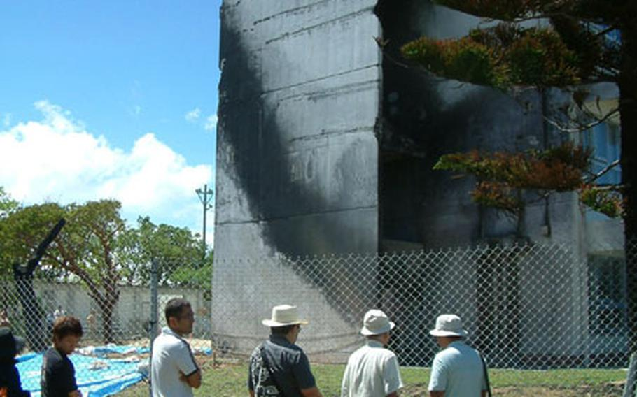 Participants in Sunday's rally at Okinawa International Univerity stop by the school's Administration building to view the blackened end where a helicopter clipped the building and crashed, bursting into flames. More than 30,000 people attended the rally, said Ginowan city officials, who hosted the event.