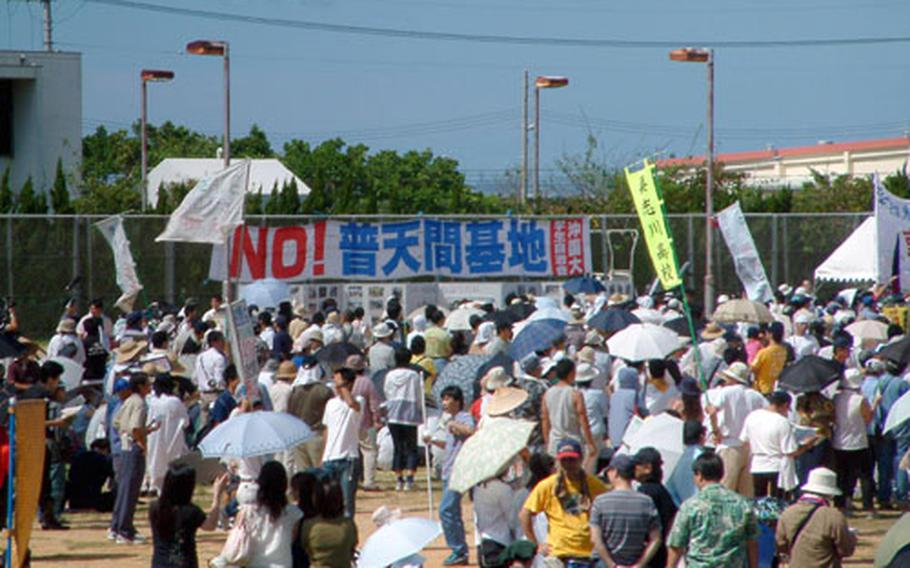 """Dozens of banners like this one, stating, """"No to the Futenma Air Station,"""" were on display on the athletic field at Okinawa International Univerity during a protest Sunday. The event was sponsored by the city of Ginowan, whose mayor has called for early closure of the air base following a crash of a Marine helicopter at the university Aug. 13. City officials said some 30,000 people attended the rally."""