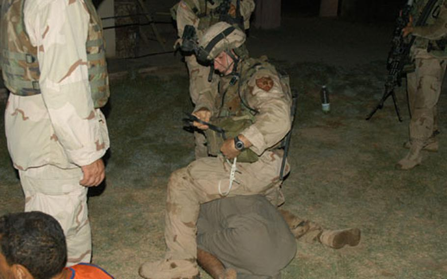 A soldier from Company C, 1st Battalion, 506th Infantry Regiment zipper cuffs an Iraqi man who resisted soldiers during house raids in Abu Fleis, Iraq, on Sunday. The man was later released.