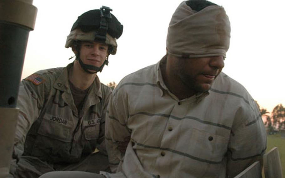 A soldier from Company C, 1st Battalion, 506th Infantry Regiment guards a detainee captured in house raids in Abu Fleis, Iraq, on Saturday as he rides to a detention facility at Camp Habbaniyah, Iraq.