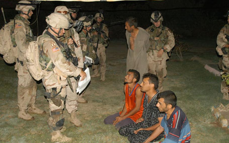 Capt. William Jones, the Company C, 1st Battalion, 506th Infantry Regiment commander, interrogates Iraqi men during house raids in Abu Fleis, Iraq, on Saturday.