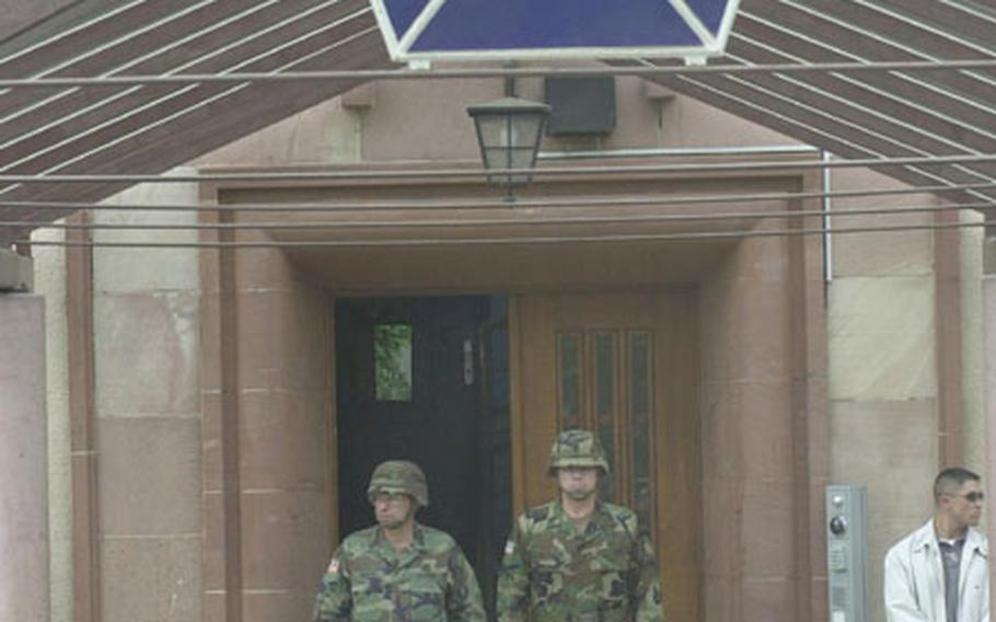 Lt. Gen. Ricardo Sanchez, left, and Command Sgt. Maj. Michael Bush wait under the awning of the V Corps headquarters as troops prepare to welcome Bush as corps' top enlisted soldier during a ceremony Monday.