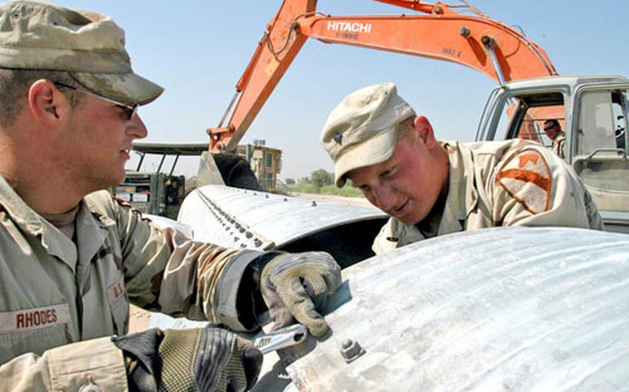 Spc. Matthew Rhodes, left, and Spc. Christian Kessler work to hook together lengths of drainage pipe on Camp Victory. The pipe was eventually used under a new roadway along the camp's perimeter.