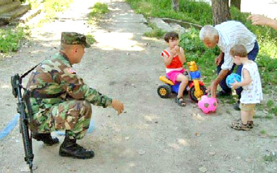 Spc. Doug Bullock plays ball with some of his neighbors in Valsenica. He is among the members of the Indiana National Guard living in a house in the Serb area of country.