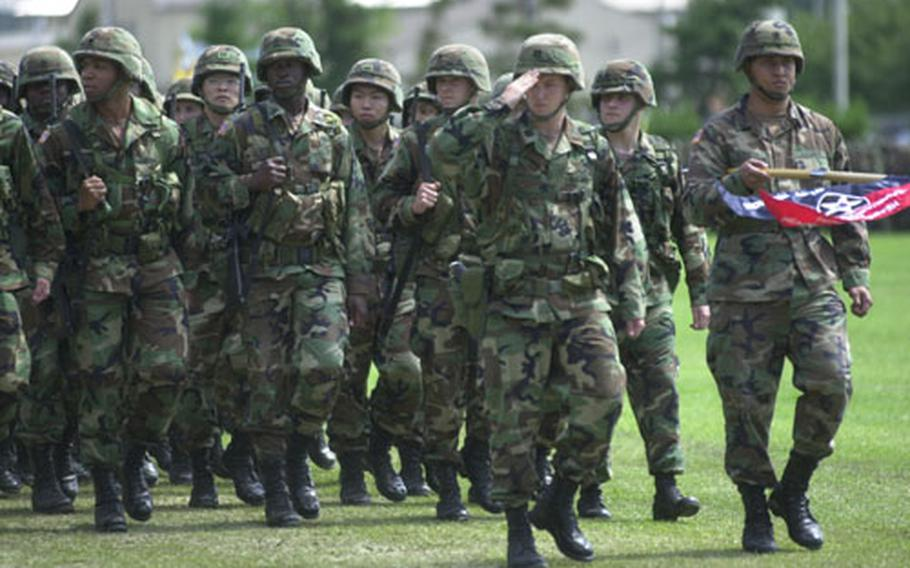 """2nd Infantry Division soldiers march in the """"pass in review"""" Tuesday as Maj. Gen. George A. Higgins assumes command."""