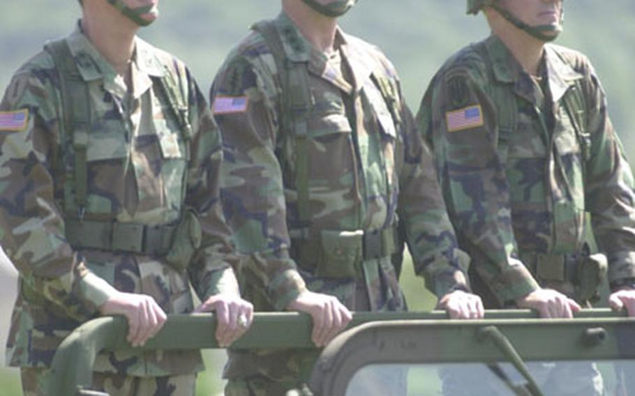 From left to right, Maj. Gen. George A. Higgins, Lt. Gen. Charles C. Campbell and Maj. Gen. John R. Wood ride in an open Humvee to inspect the 2nd Infantry Division troops Tuesday at Camp Casey.