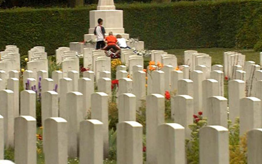 Visitors to the Osterbeek War Cemetery in the Netherlands examine the monument surrounded by the 1,754 graves of Allied servicemembers. Most were killed trying to capture the nearby bridges in Arnhem during World War II's Operation Market Garden in 1944.
