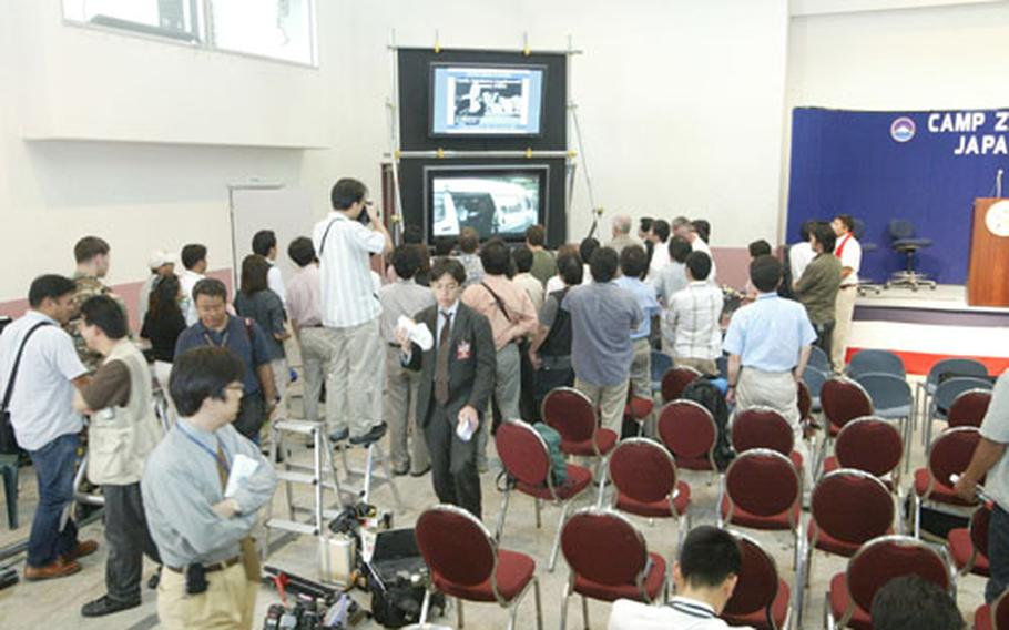 International media members at the Joint Information Bureau set up last Saturday in Camp Zama's Community Cultural Center observe the video upload on the United States Army Japan Web site.