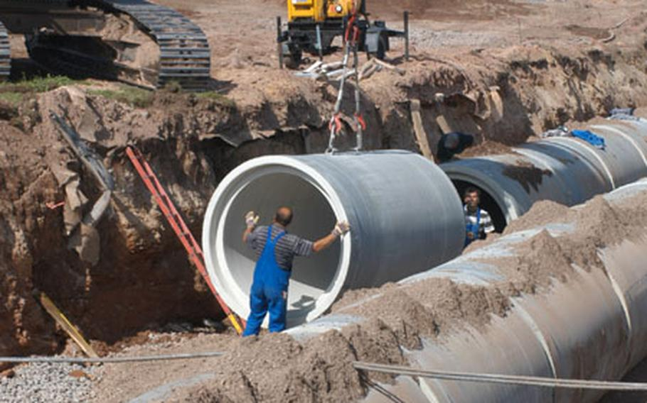 """Workers lay drainage pipe at the west end of Ramstein Air Base's runway in a 15-foot trench Air Force officials called """"the big ditch."""" The ditch is part of a $2 million project to repair the runway."""