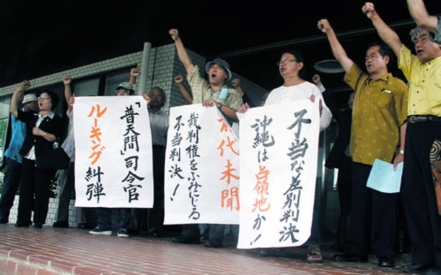 Ginowan residents and their supporters stage a brief protest rally Thursday outside the Okinawa City branch of the Naha District Court in Okinawa City. They staged the rally after their lawsuit against Col. Richard Lueking, commanding officer of Marine Corps Air Station Futenma, was dismissed.