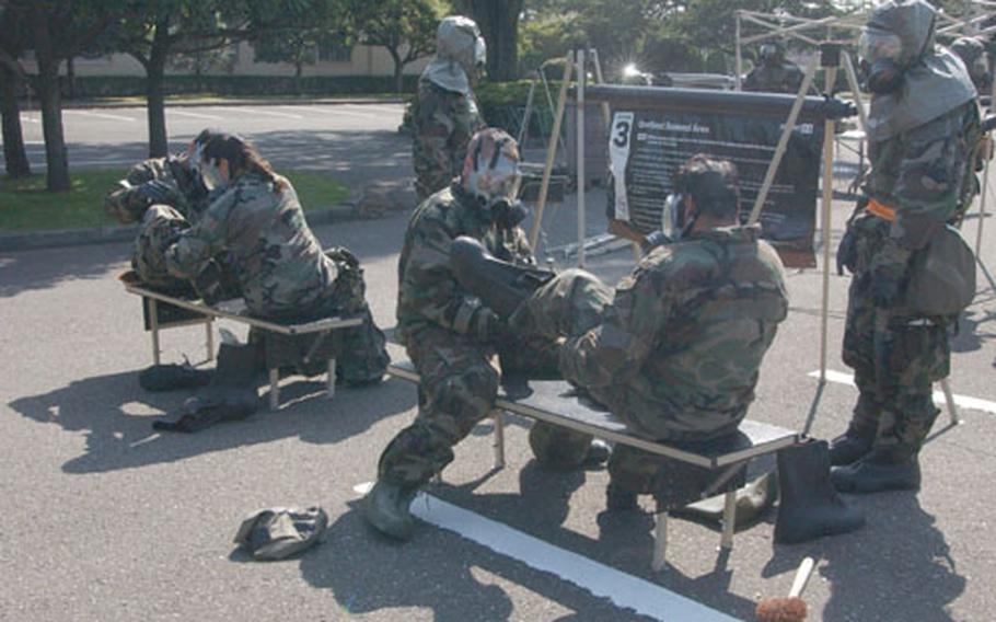 More than 30 Yokota airmen process through a decontamination line Thursday during the wing's Operational Readiness Exercise at Yokota Air Base, Japan.