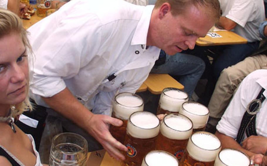 Mmmmm... beer. A waiter delivers beers to a table Saturday on the first day of the 2004 Oktoberfest in Munich, Germany.