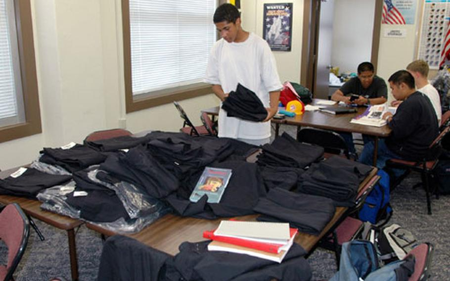 Byrrh Bryant, a 9th grade student in the Navy Junior Reserve Officer Training Corps at Sasebo Naval Base's Ernest J. King High School, looks for uniform pants in his size Thursday as JROTC cadets were fitted for their uniforms.