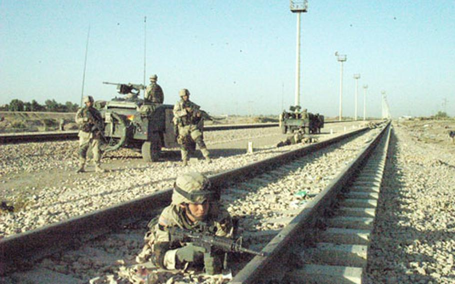 Pvt. Joshua Molt of Company D, 1st Battalion, 503rd Infantry Reigment takes cover along a railway track in Ramadi, Iraq, during fighting with insurgents Thursday.