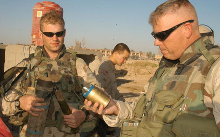Staff Sgt. William McInnis, left, and 1st Sgt. Keith Adams of Company D, 1st Battalion, 503rd Infantry Regiment, examine a cache of explosives seized in Ramadi, Iraq, on Thursday.