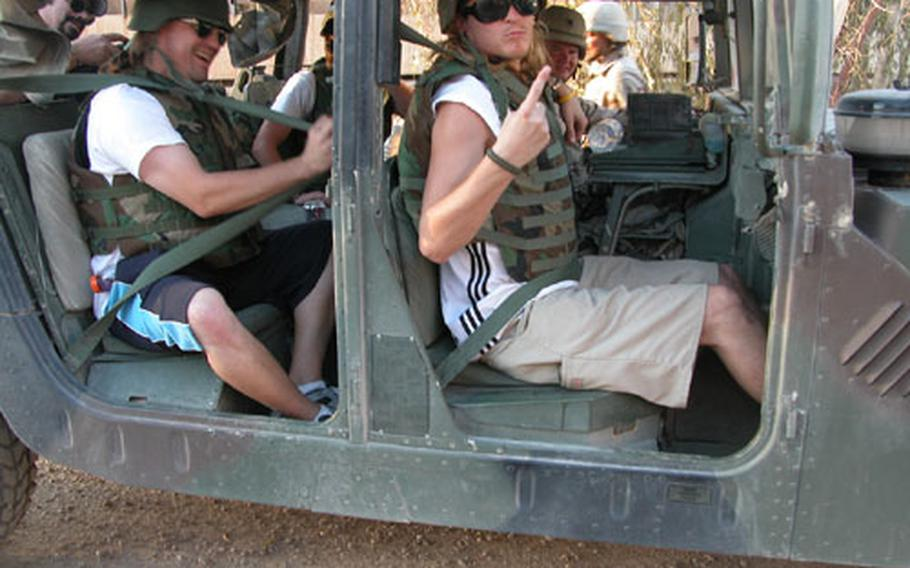 Members of the rock band Puddle of Mudd don body armor and climb into a Humvee as they get a lift to their concert for the troops at FOB Speicher last Sunday. At least 1,500 soldiers attended the show.
