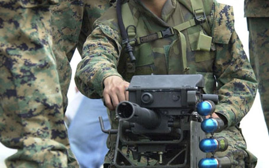 Pfc. Steven Nguyen pulls the handle of an MK-19 automatic grenade launcher during a briefing for the weapon Friday during the Cloud Warrior 2004 exercise at Camp Fuji. Members of Marine Wing Support Squadron 171 from Iwakuni Marine Corps Air Station this week are wrapping up the exercise.