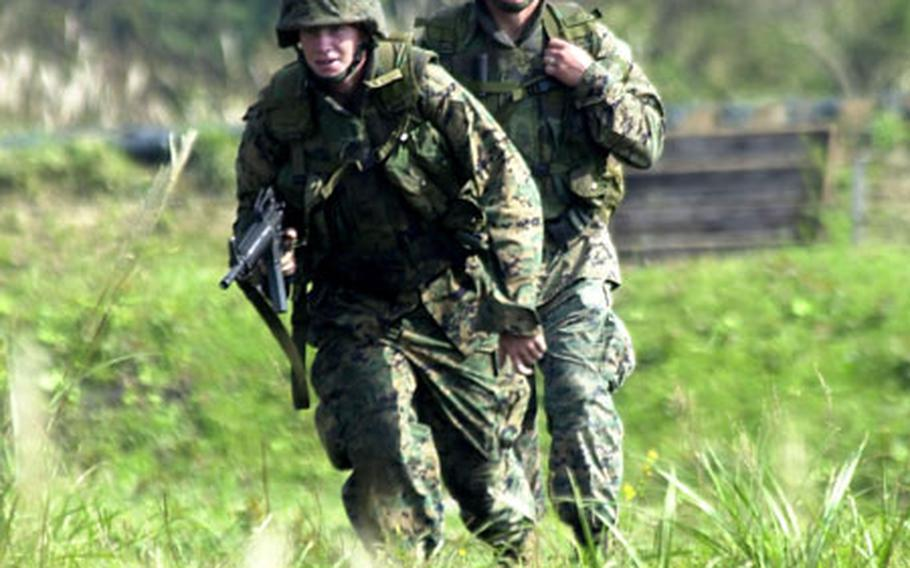 Lance Cpl. Austin Bott, left, advances as Cpl. Jedediah Rice watches Friday during exercise Cloud Warrior 2004 at Camp Fuji.