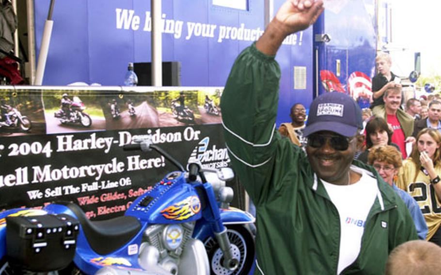 Tech Sgt. John Green, a cargo specialist with the 38th Aerial Port Squadron, comes forward waving the winning ticket stub to claim his new Harley-Davidson motorcycle Sunday afternoon in Vogelweh, Germany.