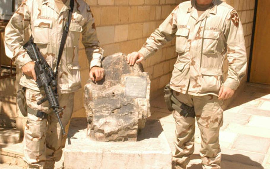 1st Battalion, 503rd Infantry Regiment Command Sgt. Maj. Jeff Sheesley, left, 43, of Alamosa, Colo., and commander Lt. Col. Justin Gubler, 40, of Honolulu, with the rock from Corrigador at Camp Habbaniyah, Iraq.