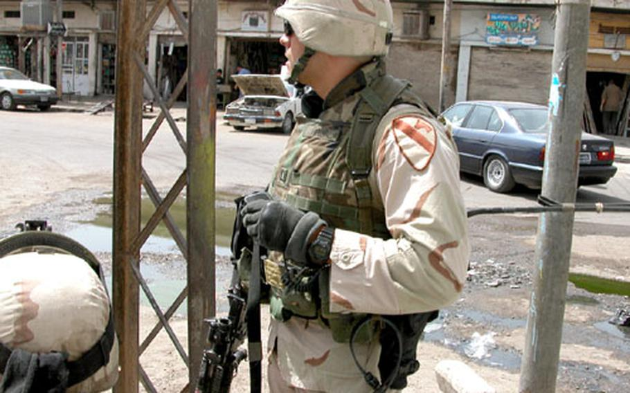 Capt. Chris Ford, commander of Company C, 1st Battalion, 9th Cavalry Regiment, tries to discern the direction of a volley of gunfire as he prepares to lead a foot patrol Sunday on Haifa Street in Baghdad.